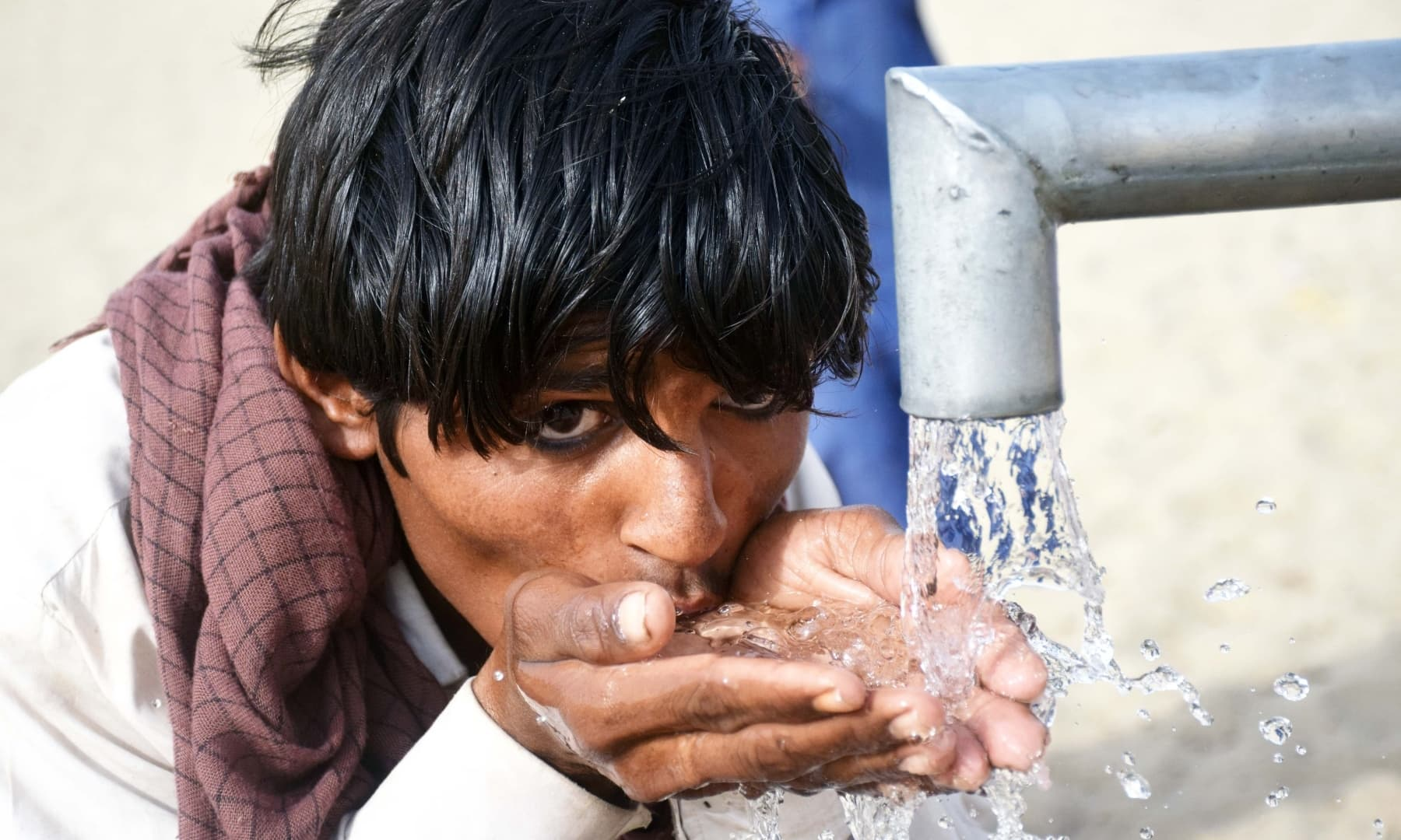 A man drinks water from a well in Achhro Thar, Khipro, Sindh. — Photo by Umair Ali