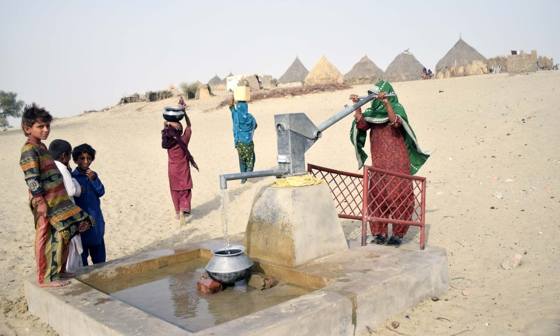 Women and children fetch water from a well in Achhro Thar, Khipro, Sindh. — Photo by Umair Ali