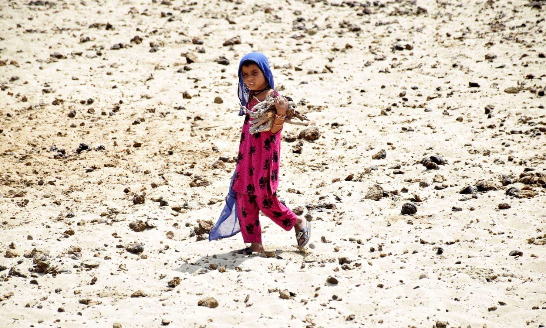 A child walks on barren and arid land in Achhro Thar, Khipro, Sindh. — Photo by Umair Ali