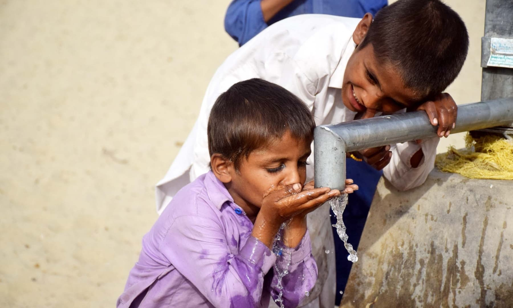 Children drinking water from a well in Achhro Thar, Khipro, Sindh. — Photo by Umair Ali