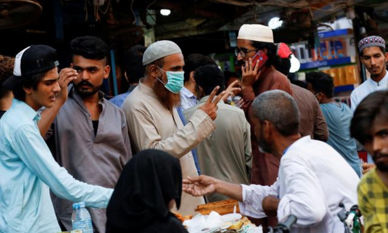 A man wears a protective face mask as he gestures while shopping amid the rush of people outside an electronics market in Karachi. — Reuters/File