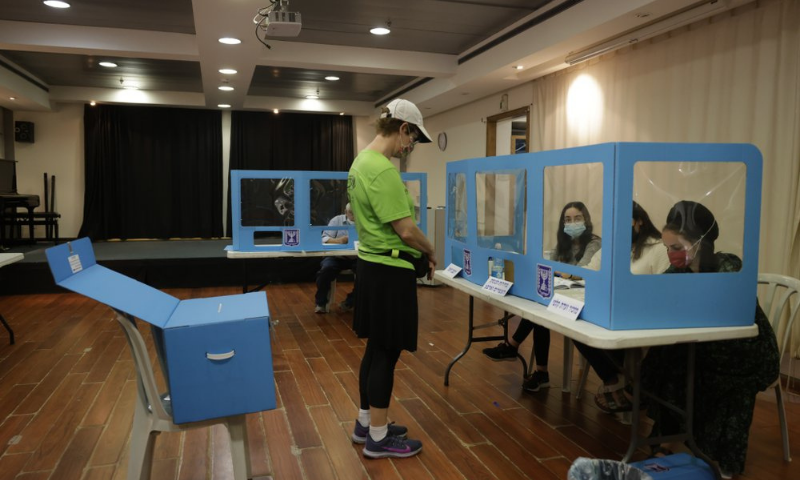 A woman arrives to vote for Israel's parliamentary election at a polling station in Ra'anana, Israel on Tuesday. — AP