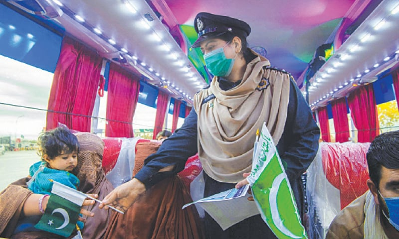 PESHAWAR: A policewoman distributes national flags among passengers in a bus to mark Pakistan Day on Tuesday.—AFP