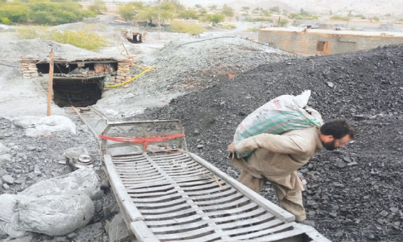 Dilbar Khan Swati carrying a coal-filled sack at the depot in Mach.—Photo by writer