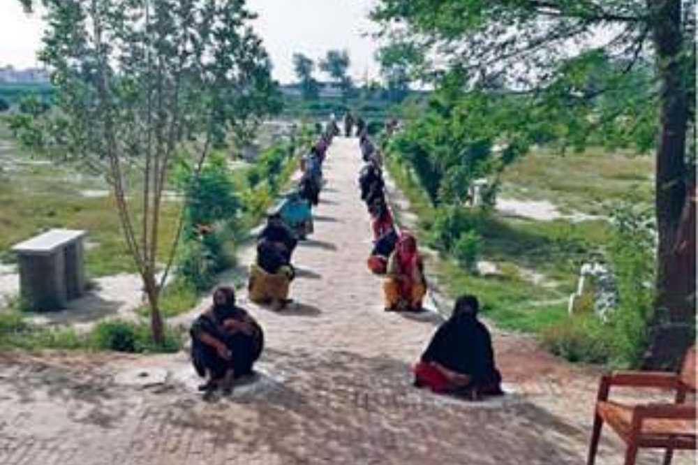 In this file photo, women sit on ground in Faisalabad prior to getting financial assistance under the Ehsaas programme. — File
