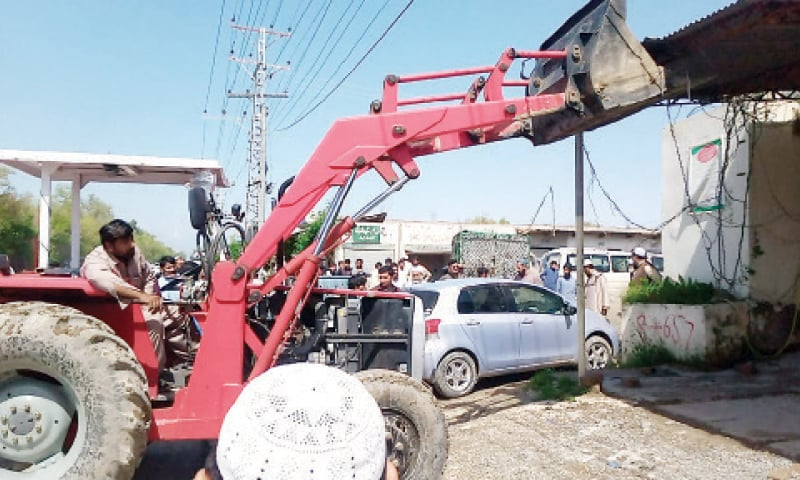 A machine removes illegal structures along Naserkhel canal during a campaign in Naurang City, Lakki Marwat, on Wednesday. — Dawn