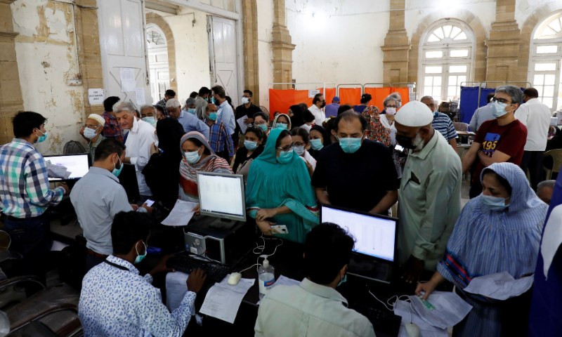 People gather for their coronavirus vaccine doses, at a vaccination centre in Karachi on  Monday. — Reuters/File