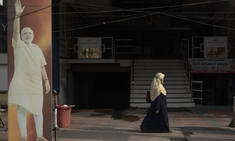An Indian Muslim woman walks past an image of Prime Minister Narendra Modi displayed outside an office of the Bharatiya Janata Party in Kochi, Kerala state, India, 2021. — AP