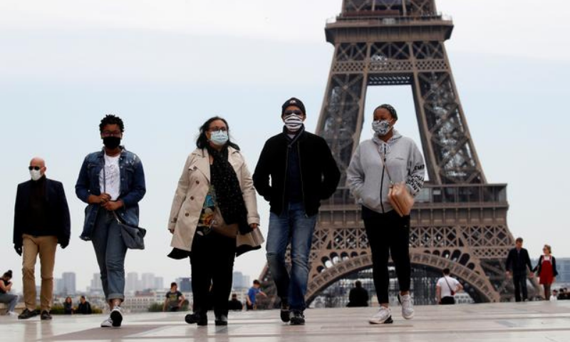 People wearing face masks walk at Trocadero square near the Eiffel Tower. — Reuters/File