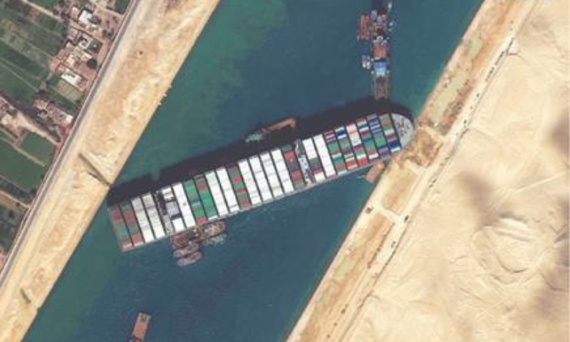 This satellite imagery released by Maxar Technologies shows tug boats and dredgers on Saturday attempting to free the Taiwan-owned MV Ever Given lodged sideways and impeding all traffic across Suez Canal. — AFP