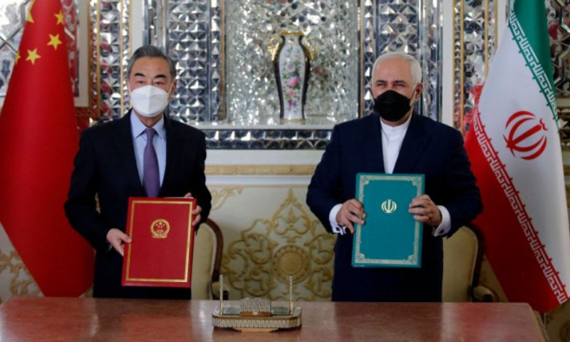 Iranian Foreign Minister Mohammad Javad Zarif (R) and his Chinese counterpart Wang Yi, pose for a picture after signing an agreement in the capital Tehran. — AFP