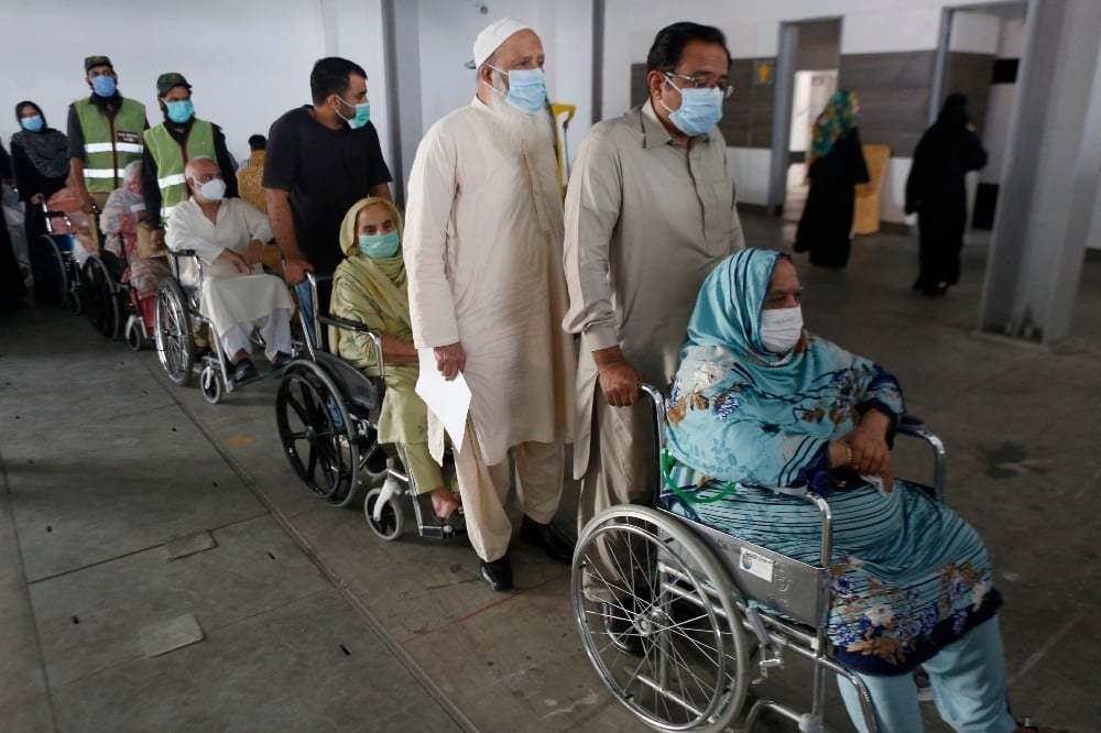 Senior citizens wait their turn to receive the Sinopharm coronavirus vaccine from a health worker at a vaccination center in Lahore on March 18. — AP