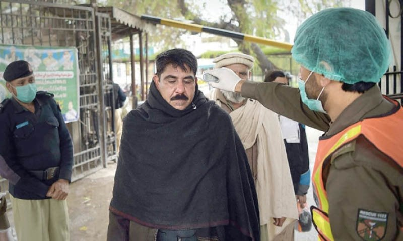A Rescue 1122 worker scans employees at Civil Secretariat, Peshawar. — White Star/File