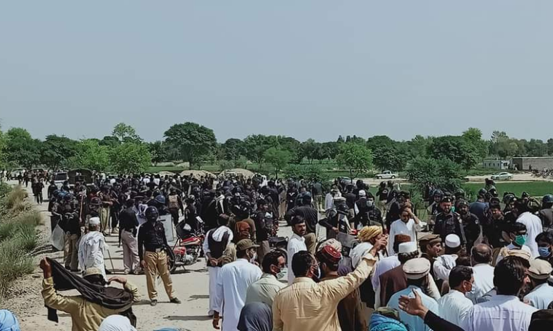 Protesters from the Janikhel area of Bannu are seen during their march while policemen are also present. — Photo by Sirajuddin