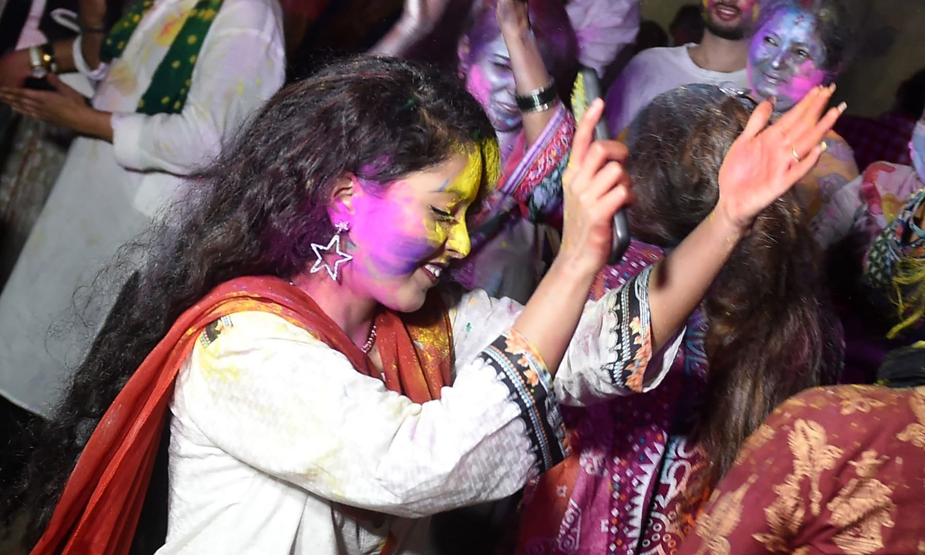 Revellers dance during Holi celebrations in Karachi on Sunday. — AFP
