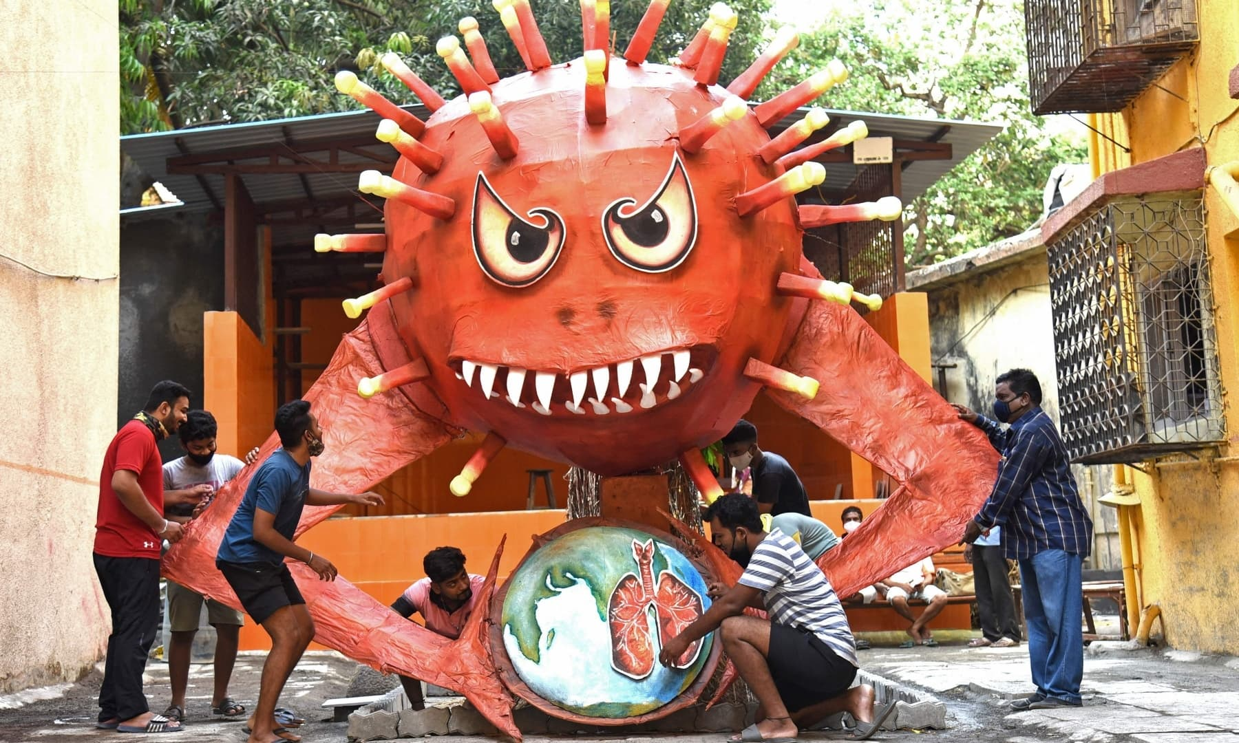 People are seen near a giant effigy resembling the Covid-19 coronavirus to be burned as part of Holika Dahan, in Mumbai on March 28. — AFP