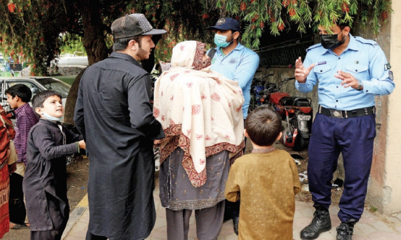 A police official stops a family from entering a weekly bazaar in Aabpara on Sunday for not wearing masks. — Photo by Mohammad Asim