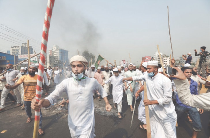NARAYANGANJ (Bangladesh): Activists of Islamist group Hefazat-i-Islam, wielding sticks and chanting anti-government slogans, enforce a daylong strike on Sunday.—AP