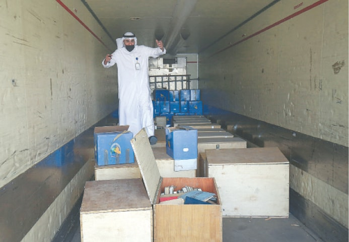 AN employee at the Kuwaiti information ministry inspects boxes in the back of a truck containing Kuwaiti archives seized during the Iraqi invasion in 1990.—AFP