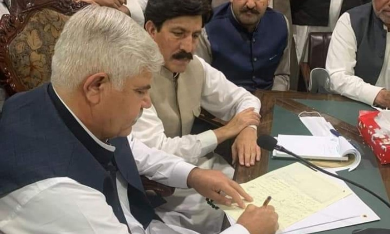 Khyber Pakhtunkhwa Chief Minister Mehmood Khan signs the settlement with the protesters. — Photo provided by Sirajuddin