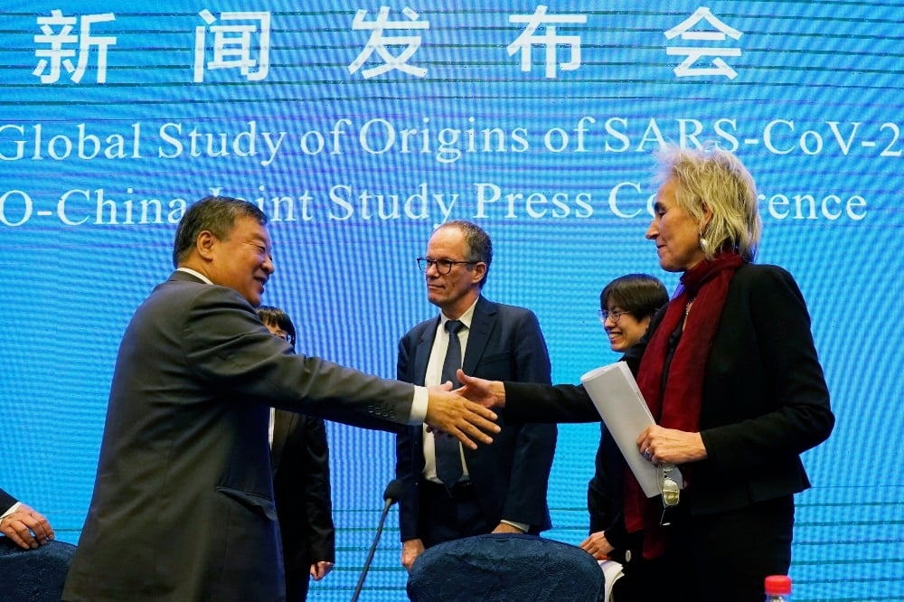 In this Feb 9 file photo, Marion Koopmans, right, and Peter Ben Embarek, center, of the World Health Organization team say farewell to their Chinese counterpart Liang Wannian, left, after a WHO-China Joint Study Press Conference at the end of the WHO mission in Wuhan. — AP