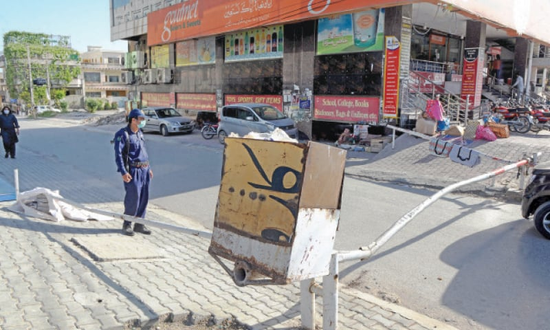 A guard stands near a barrier in PWD Colony Block C which was sealed on Monday after emergence of Covid-19 cases. — Photo by Mohammad Asim
