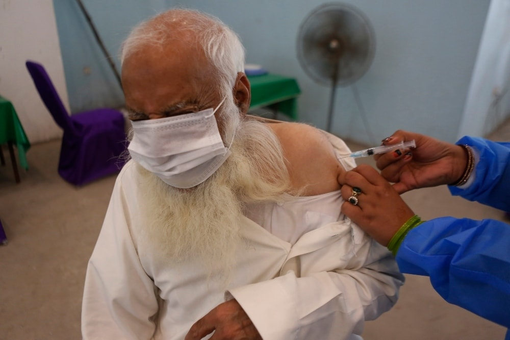 A man reacts while receiving a Sinopharm coronavirus vaccine from a health worker at a vaccination center in Lahore on March 29. — AP