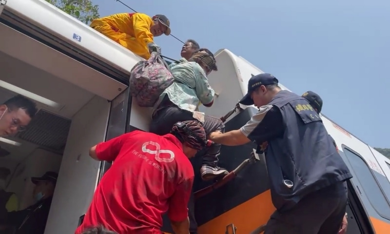 Rescue team help one of the stranded passengers down from the roof of a train which derailed in a tunnel north of Hualien on April 2. — Reuters