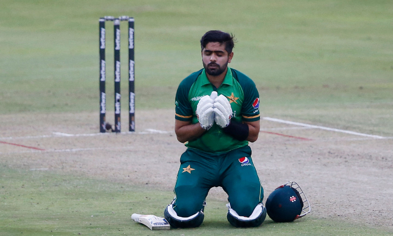 Captain Babar Azam kneels down while celebrating after scoring a century during Friday's match. — AFP