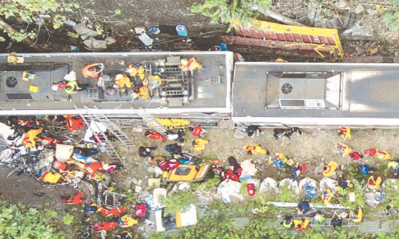 RESCUERS work at the site of a train crash that was caused by a maintenance vehicle (top yellow) which slipped down an embankment above the tracks in the mountains of Hualien, eastern Taiwan, on Friday.—AFP