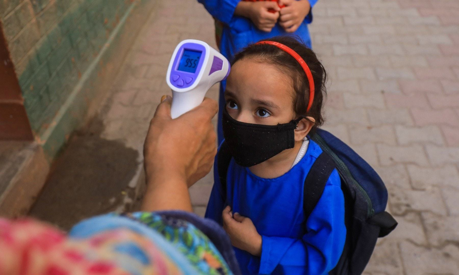 A student wears a protective mask as she gets her temperature checked before entering a class in Peshawar on September 30, 2020. — Reuters/File