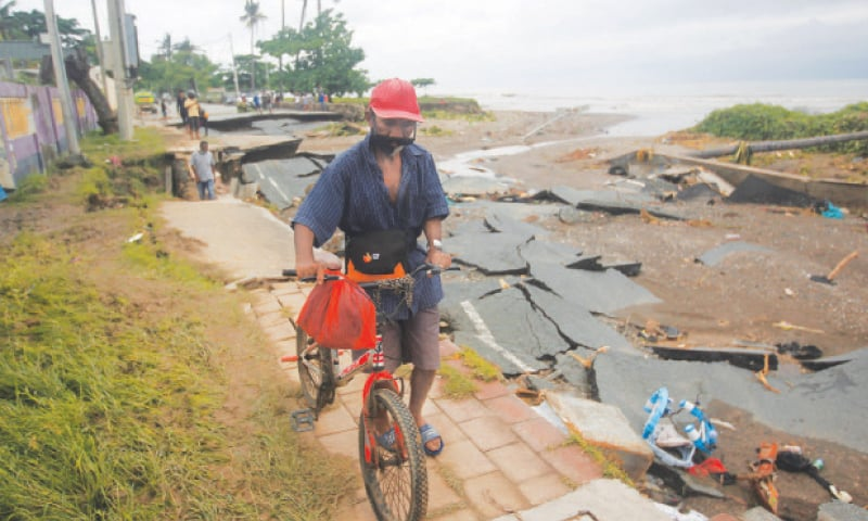 A MAN wheels his bicycle through a road damaged by floods after heavy rains in Dili, East Timor, on Monday.—Reuters