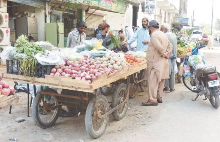 People buy vegetables from a vendor in a city locality.—White Star