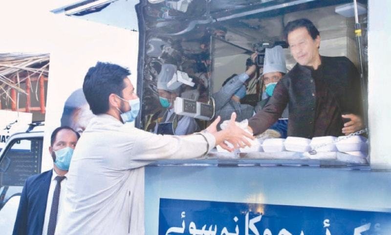 In this file photo, Prime Minister Imran Khan distributes food packets at the launch of 'Koi Bhuka Na Soye' initiative in Islamabad. —White Star/File