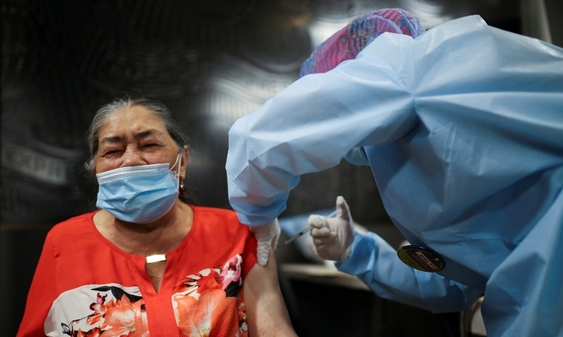 A woman receives her first dose of China's Sinovac Biotech vaccine during a mass vaccination program for the elderly at Movistar Arena in Bogota on March 9. — Reuters