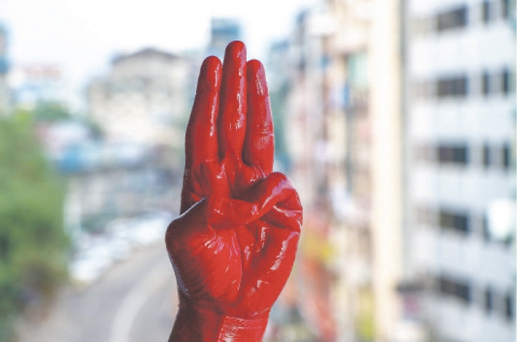 YANGON: A protester shows the three-fingered salute of resistance on his red painted hand in memory of the people who died during previous demonstrations on Tuesday.—AP