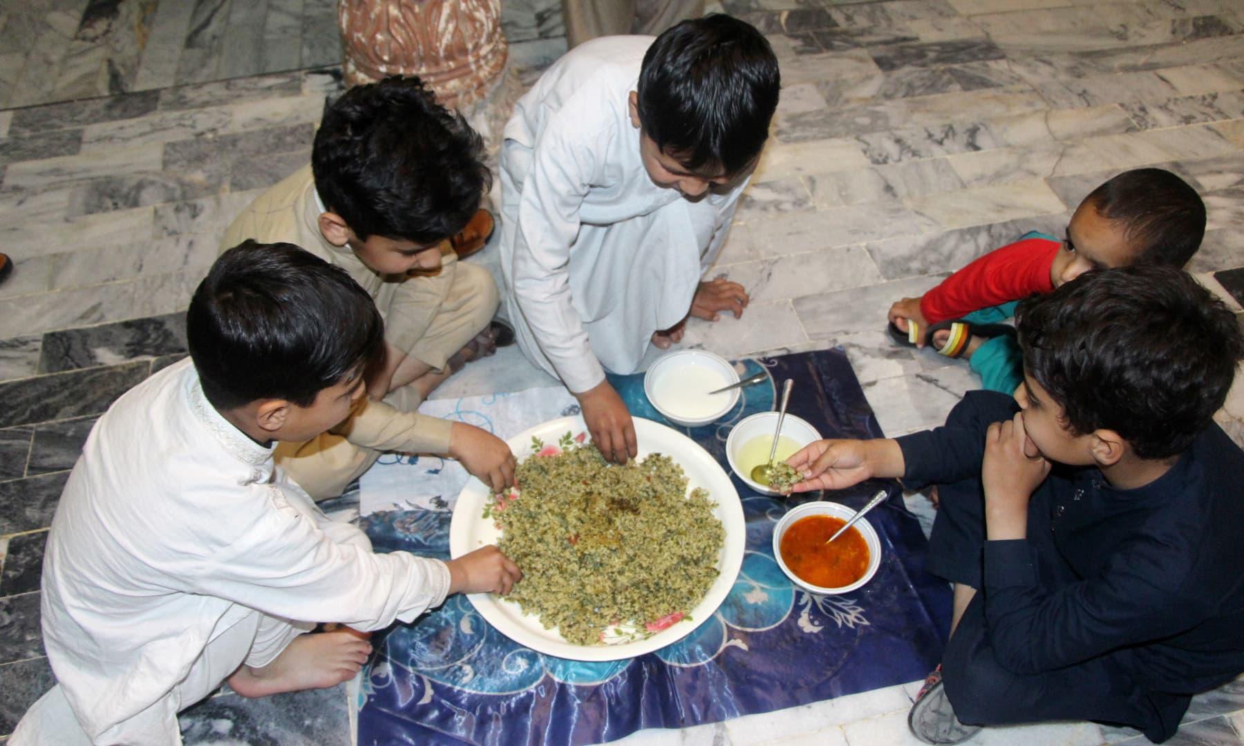 بچے روایتی کھانا تناول فرما رہے ہیں— امجد علی سحاب