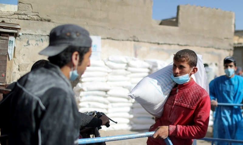 A Palestinian worker carries a bag of flour outside an aid distribution centre run by United Nations Relief and Works Agency (UNRWA), at Beach refugee camp in Gaza City, April 7, 2021. — Reuters