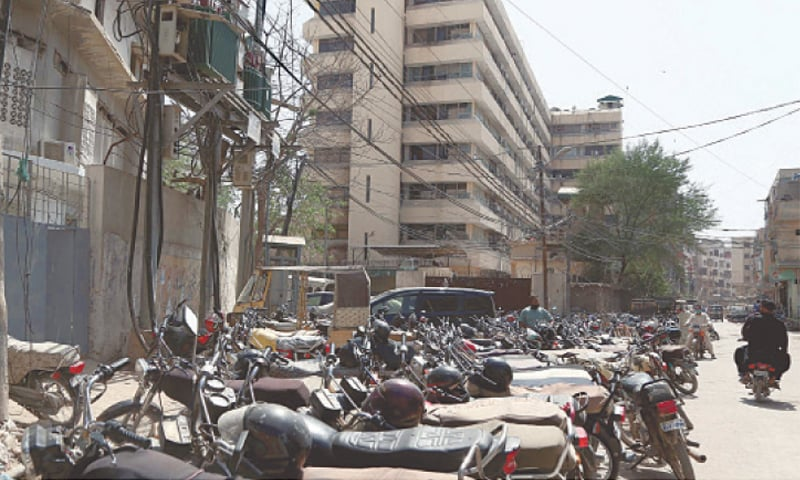 Haphazardly parked vehicles, as seen here near Sindh Secretariat, also add to traffic congestion.—PPI