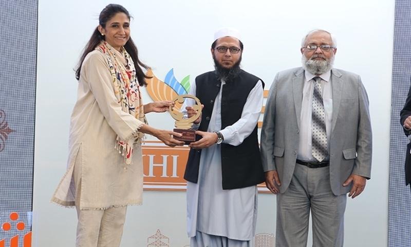Naz Khan presenting award to Saad Ahmed Qazi