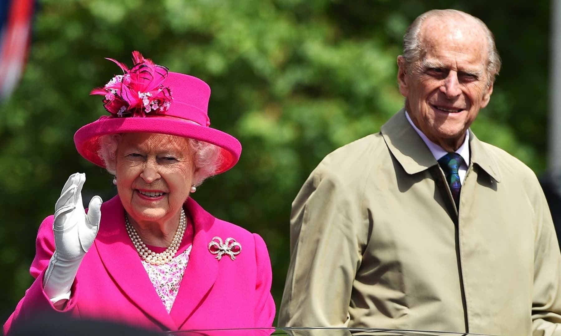 Queen Elizabeth II and Prince Philip wave to guests from their car as they attend the Patron's Lunch on the Mall, an event to mark her official 90th birthday in London. — AFP/File
