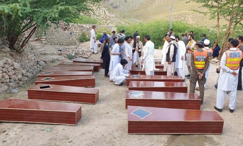 Families of the slain miners and local political leaders stand next to their coffins in Dara Adamkhel on Friday. — Photo by author