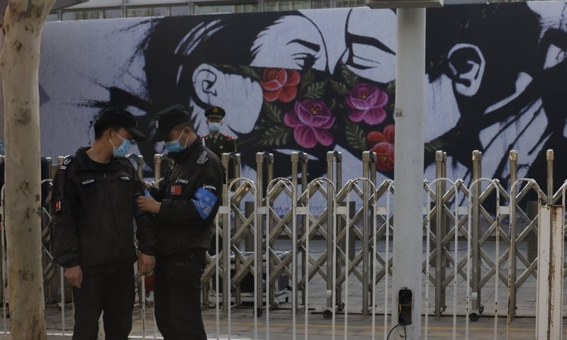 Chinese security personnel stand on duty near an art work outside the United States Embassy in Beijing on April 6. — AP