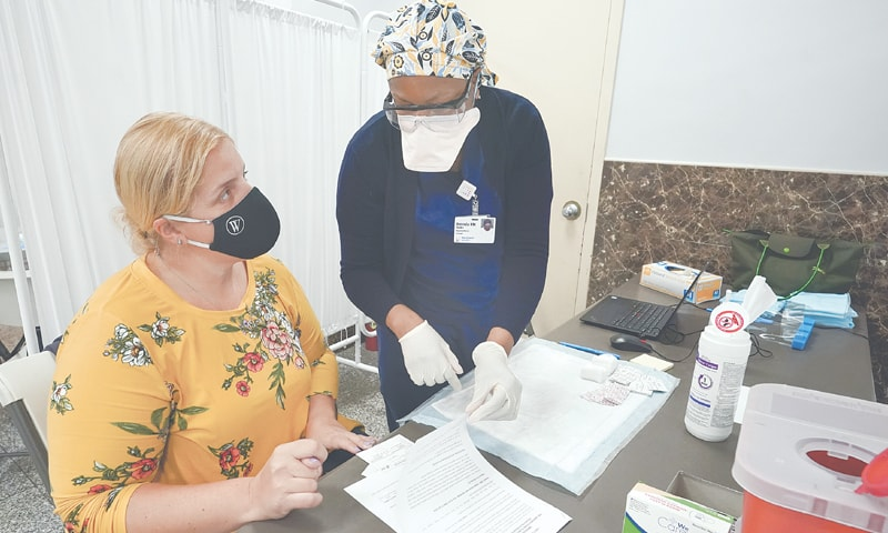 A REGISTERED nurse goes over the paper work with mosque member Zejreme Rodoncic after inoculating her with the Johnson & Johnson Covid-19 vaccine at the Albanian Islamic Cultural Centre in the Staten Island borough of New York. Ahead of Ramazan, religious leaders are using social media platforms and face-to-face discussions to explain that it's acceptable for Muslims to be vaccinated during fasting.—AP