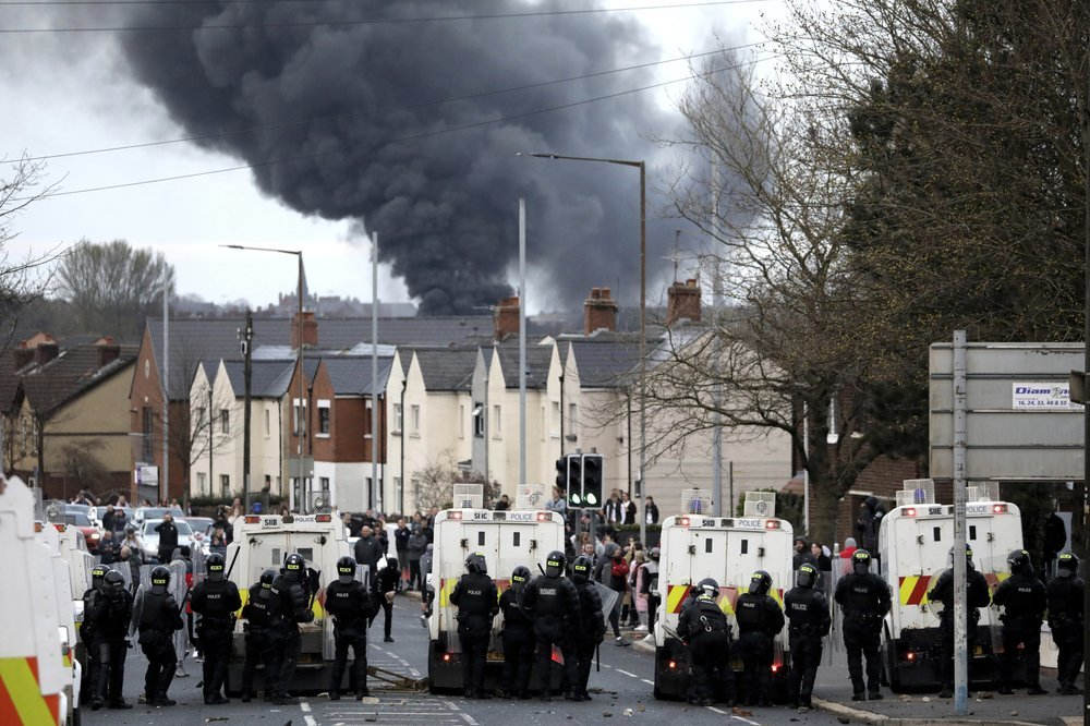 In this April 7 photo, police form a line on the Springfield road to stop Nationalists and Loyalists attacking each other, as a hijacked bus burns in the distance in Belfast, Northern Ireland. — AP