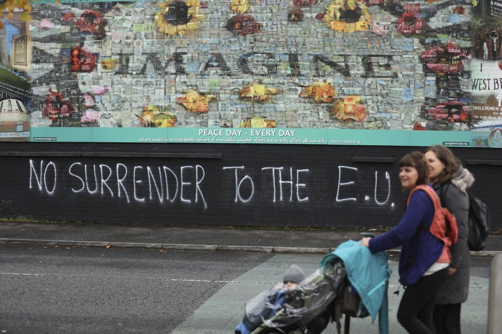 In this Oct 14, 2019 file photo, people walk past pro-Brexit graffiti in West Belfast. — AP