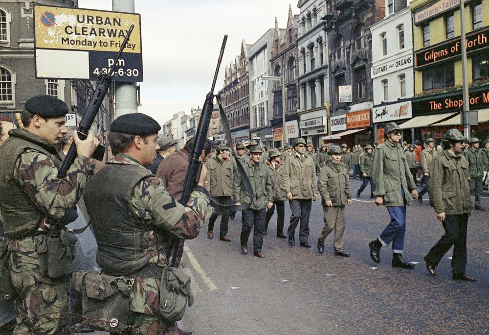 In this August 1972 file photo, British troops watch as members of the Ulster Defence Association parade through Belfast, Northern Ireland. — AP
