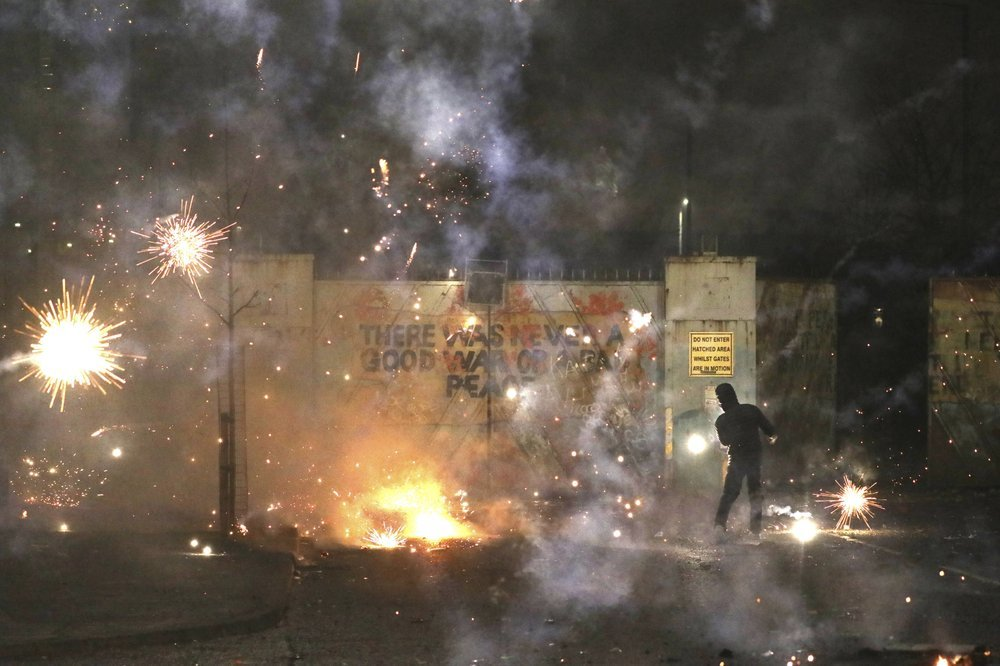 In this April 7 photo, a firework explodes as Nationalist and Loyalist rioters clash with one another at the peace wall on Lanark Way in West Belfast. — AP