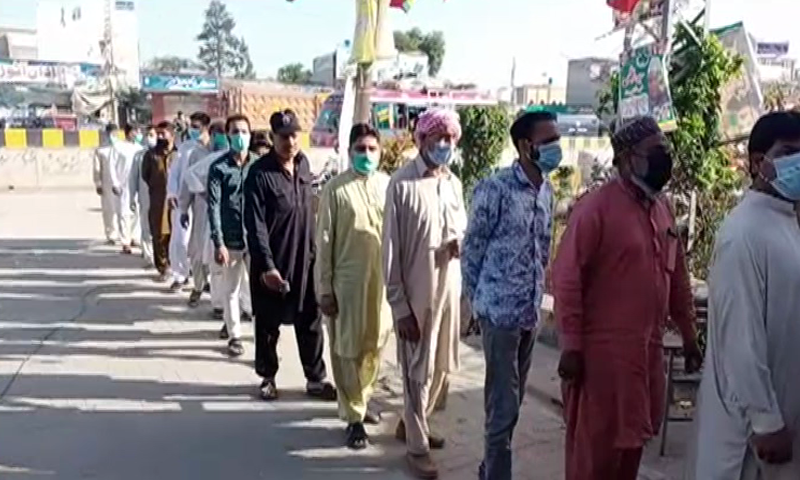 People in line to cast their votes in NA-75 re-election. — DawnNewsTV
