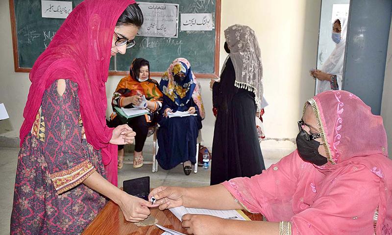 ضمنی انتخابات میں خاتون کی جانب سے ووٹ کاسٹ کیے جانے کے بعد پریذائیڈنگ آفیسر ان کے انگوٹھے پر نشان لگا رہی ہیں— فوٹو: اے پی پی
